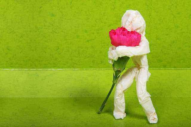 Χάρτινο ανθρωπάκι που αγκαλιάζει λουλούδι